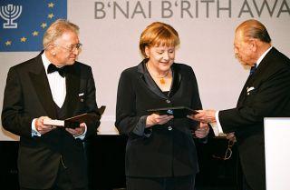 Mars 2008 : Reinold Simon, Président du B'nai B'rith Europe, et Joseph H. Domberger, Président d'Honneur du B'nai B'rith Europe, ont accompagné la Chancelière sur la scène pour lui remettre la Médaille d'Or du B'nai B'rith Europe pour services humanitaires (source BBE)
