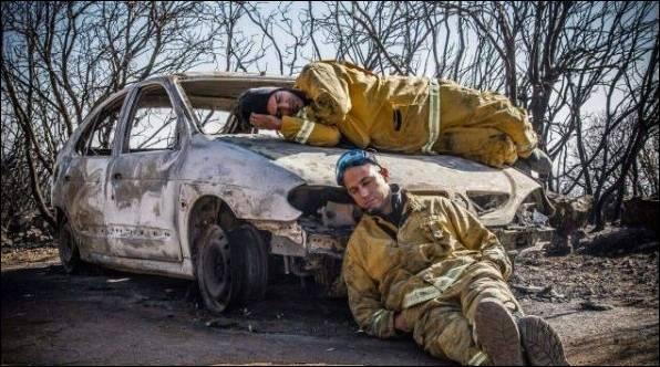 Deux pompiers Israéliens se reposent sur une voiture calcinée après avoir combattu sans arrêt pendant 5 jours les incendies - Merci à ces soldats du feu